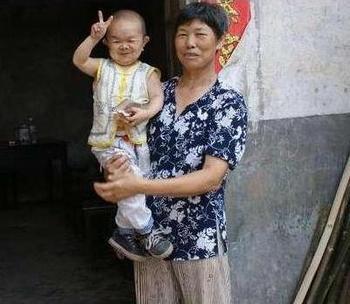 Претендент на рекорд Книги Гиннеса, 40-летний Хуан Кайцюань на руках у своей мамы. Фото с epochtimes.com