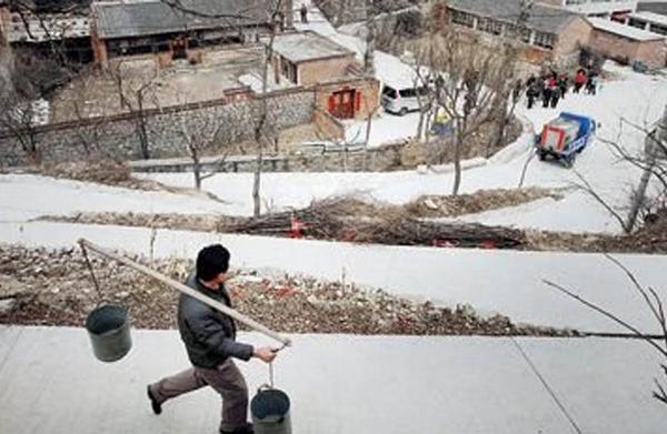 Засуха в Китае. Житель деревни пригорода Пекина идёт за водой, которую привозят утром на машине. Февраль 2011 год. Фото с epochtimes.com