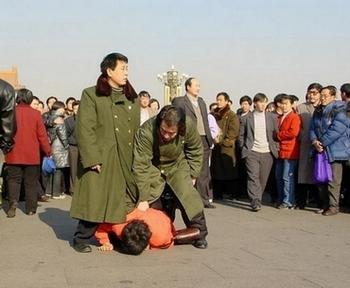 Китайские сотрудники спецслужбы прямо на улице арестовывают последователя Фалуньгун. Фото с minghui.com