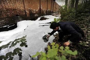Китайский эколог берёт пробы воды в водоёме рядом с заводом в провинции Хэнань. Фото: Getty images