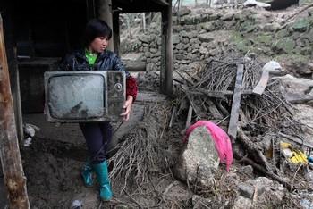 Жительница деревни провинции Хубэй спасает от наводнения своё имущество. 15 мая 2010 год. Фото: AFP
