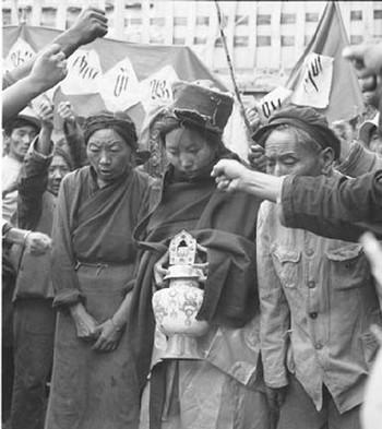 В начальный период оккупации компартией Тибета, практически каждый день проходили публичные акты «критики и нападок» по отношению к высшим ламам и чиновникам бывшего тибетского правительства. На фото публичным нападкам подвергается самая известная в Тибете женщина-лама (с кувшином в руках), и её родители. Фото с epochtimes.com