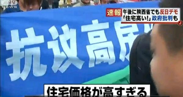 Во время антияпонской акции протеста появились плакаты против высоких цен на квартиры, коррупции и т.д. Кадр видеоролика японского телевидения
