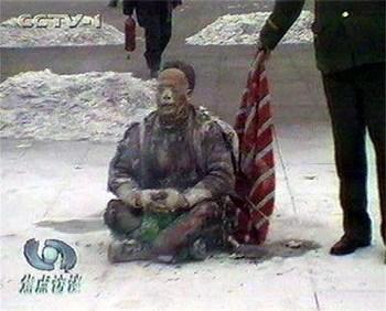 Один из многочисленных кадров инцидента «самосожжения», показанного китайским каналом CCTV, который обнажает фальсификацию. Полицейский подождал, пока сидящий «самосожженец» прокричит в камеру фразу «Фалуньгун – это хорошо», и только потом накинул на него тряпку