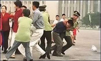 Китайские полицейские хватают последователей Фалуньгун, распространяющих на улице листовки. Фото с epochtimes.com
