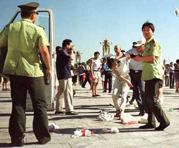 Китайские полицейские арестовывают последовательницу Фалуньгун за раздачу материалов о преследовании этой практики коммунистическим режимом КНР. Фото с epochtimes.com