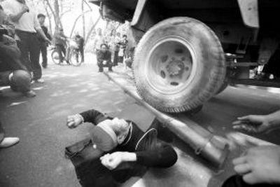 Мастер цигун Дэн Юйлань демонстрирует возможности своего тела. Город Цзинань. Апрель 2011 год. Фото: Коммерческий вестник Шаньдун