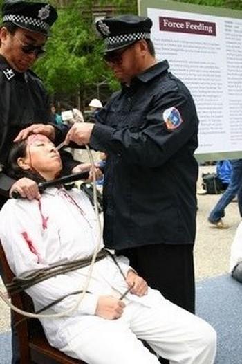 Инсценировка насильственного кормления, которое часто применяют в китайских тюрьмах к сторонникам Фалуньгун, объявившим голодовку в знак протеста. Через нос в желудок вводится трубка, через которую вливают жидкую пищу или же в качестве пытки — раствор соли или перца. Фото с epochtimes.com
