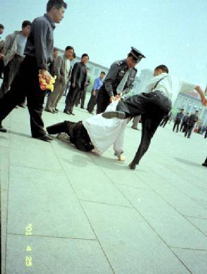 Полицейские бьют последователя практики Фалуньгун, который вышел с публичным обращением к правительству, требуя прекратить репрессии сторонников данной практики. Пекин, площадь Тяньаньмэнь. Фото: minghui.org