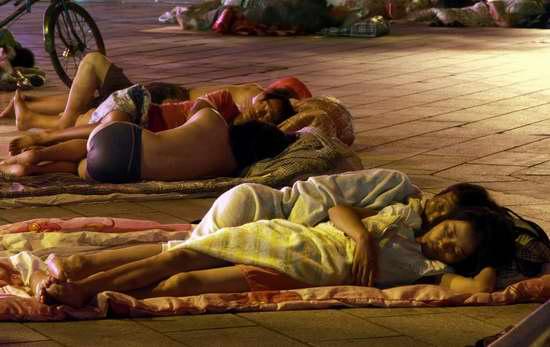 Фото: Рабочие-мигранты спят тротуарах. Город Иу провинции Чжэцзян. 5 августа 2011 год. Фото с kanzhongguo.com