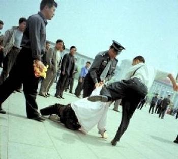 Фото: Китайские полицейские бьют последователя Фалуньгун. Фото: minghui.org