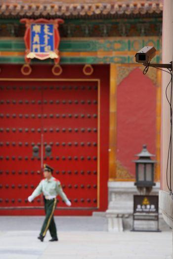 Полицейские патрулируют  18 мая вход в музей Запретного города в Пекине. В верхнем правом углу видна камера безопасности. Фото: Feng Li/Getty Images