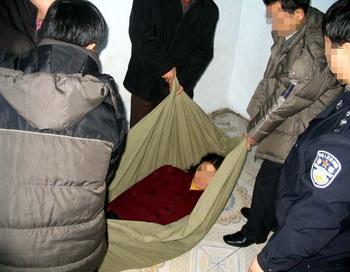 Последовательницу Фалуньгун выносят из полицейского участка. Фото с сайта Минхуэй.