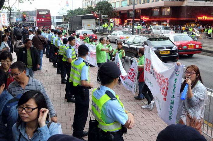 Активисты в зелёной форме с надписями на баннерах, порочащими Фалуньгун. Позднее они стали выкрикивать оскорбления последователям Фалуньгун. Фото: The Epoch Times