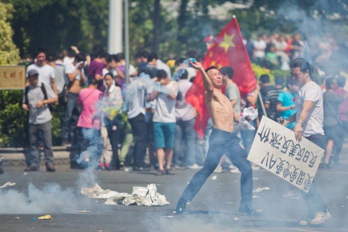Участник антияпонской акции протеста бросает дымовую шашку, 16 сентября 2012 года, Шэньчжэнь, Китай. Протесты в Китае, вспыхнувшие из-за спорных островов Сенкаку, ещё больше дестабилизируют ситуацию в регионе. Фото: Lam Yik Fei/Getty Images
