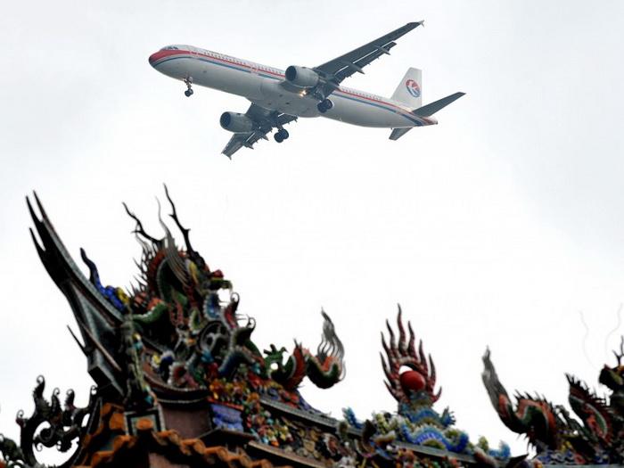 Самолёт авиакомпании China Eastern Airlines пролетает над храмом перед посадкой в Тайбэе 29 июня 2010 года. Цзэн Цинхун с 2002 года отмывал деньги через эту авиакомпанию. Фото: Patrick Lin/AFP/Getty Images