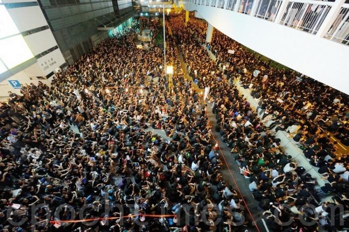 Большая толпа окружила здание правительства Гонконга в пятницу, 7 сентября. Протестующий держит плакат «Отменить». Фото: Сун Сянлун/Великая Эпоха
