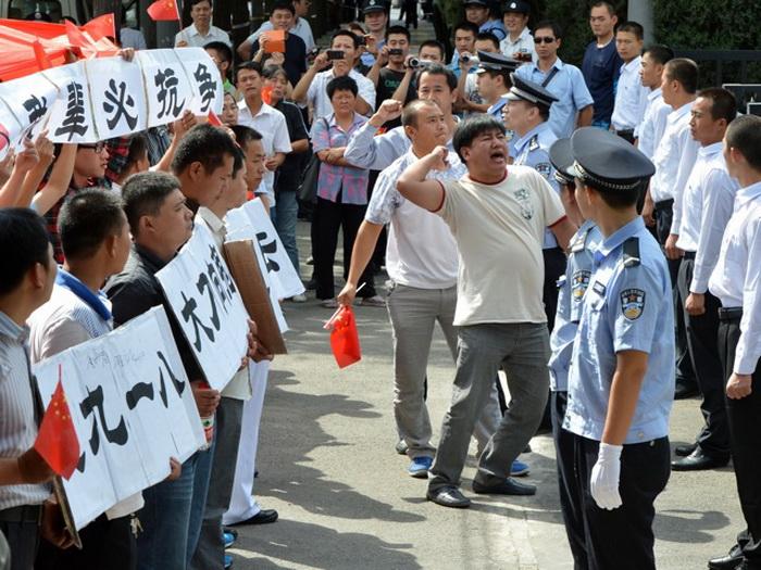 Участники антияпонской акции у японского посольства в Пекине, 13 сентября 2012 года. Некоторые китайцы начали преследовать японцев в Китае и портить автомобили японских марок, выражая протест против действий Японии, предъявляющей права на острова Сенкаку в Восточно-Китайском море. Фото: Mark Ralston/AFP/Getty Images