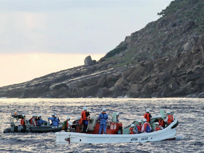 Команда японских инспекторов проводит с берега обзор лодок около острова Уотсуриджима, части спорной цепи островов, известных как Сенкаку в Японии и Дяоюй в Китае, 2 сентября 2012г. Фото: JIJI Press/AFP/Getty Images