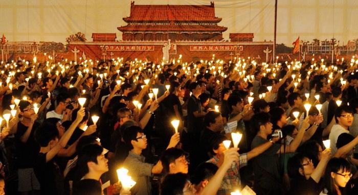 Участники акции, на которую собралось 180 тысяч людей, в годовщину бойни на площади Тяньаньмэнь держат зажжённые свечи и плакаты в память о жертвах, Гонконг. Фото: Сун Пи Лун/Великая Эпоха