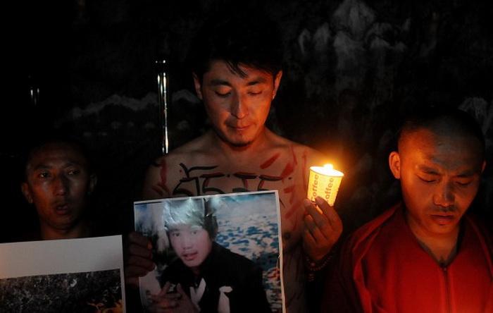 Тибетец в изгнании держит фотографию 27-летнего Сенге Гьяцо на акции с зажжёнными свечами, в знак солидарности с жертвой. В минувшие выходные в провинции Ганьсу ещё один тибетец поджёг себя.