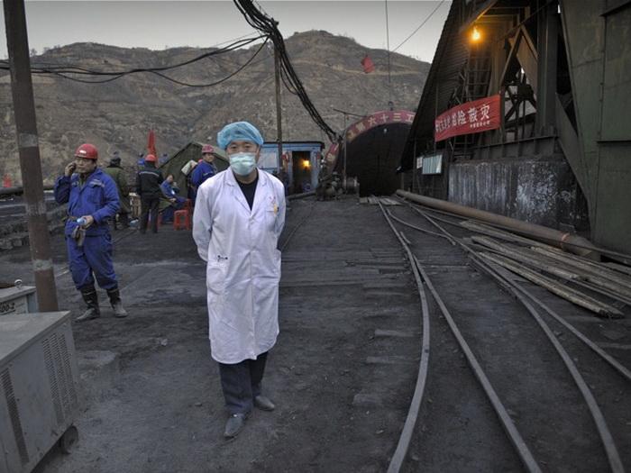 Медицинский работник стоит у входа в угольную шахту Ванцзялин, где спасли во время затопления более 110 человек. Провинция Шаньси, Китай, 5 апреля 2010 года. Фото: Peter Parks/AFP/Getty Images