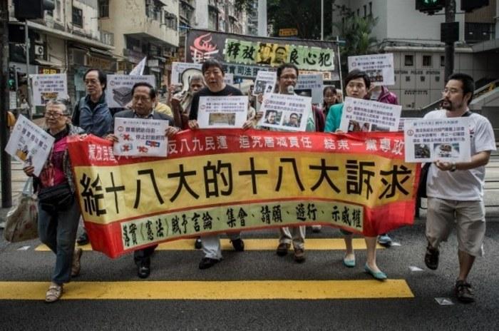Продемократический законодатель Ли Чок-ян (3-й слева) и другие демонстранты держат плакаты, направляясь к китайскому департаменту по связям, во время акции протеста против центрального правительства в Пекине, Гонконг, 8 ноября 2012 года. Фото: Phillipe Lopez/AFP/Getty Image