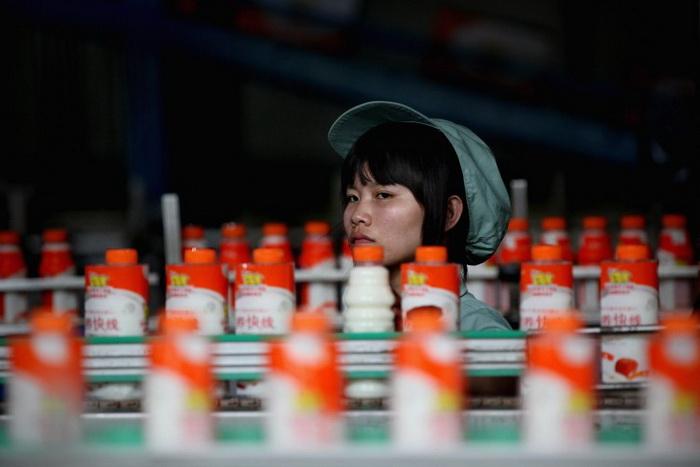 Рабочий наблюдает за наполнением бутылок молочным напитком Wahaha на поточной линии Wahaha Group Co., Ltd. 2 июля 2012г. в Ханчжоу провинции Чжэцзян, Китай. Недавно проведённые экономические расчёты  указывают на наличие избыточных производственных мощностей в промышленном секторе, а следовательно, возрастание потребительских цен. Фото: Feng Li/Getty Images