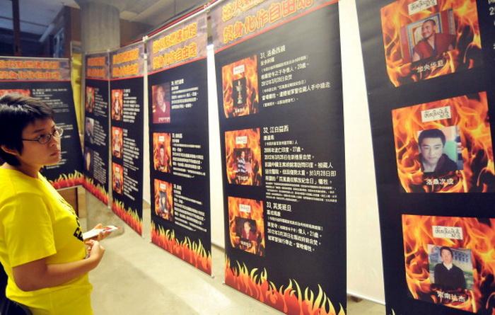 Женщина рассматривает выставку с фотографиями жертв самосожжения в Тибете. Более 50 человек совершили акт самосожжения в тибетских населённых пунктах Китая с февраля 2009 года. Фото: Mandy Cheng / AFP / GettyImages