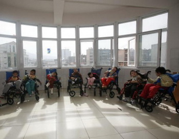 Дети, которые страдают церебральным параличом, ждут приёма пищи в благотворительном Центре для детей сирот и инвалидов в городе Синин, 24.02.2009, провинция Цинхай, Китай. Фото: China Photos/Getty Images