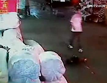 Человек проходит мимо Юэюэ через несколько секунд после того, как она попала под машину. Фото: Screenshot NTDTV