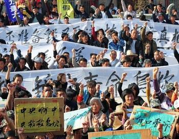 Сельские жители держат плакаты во время акции протеста в Укани провинции Гуандун 19 декабря 2011 года. Они требуют от центральной власти принять меры по поводу незаконных захватов земли и наказать виновников смерти местного активиста. Фото: STR/AFP/Getty Images