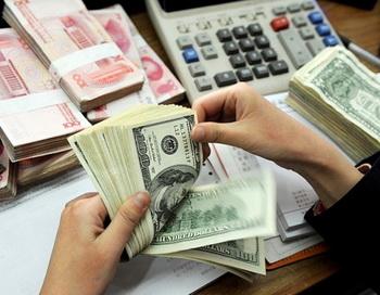 На фотографии, сделанной 16 января 2011 года, кассир, пересчитывающий пачку долларов США и 100 китайских юаней в банке в Хэбэй, на востоке Китая в провинции Аньхой. Фото: AFP/Getty Images