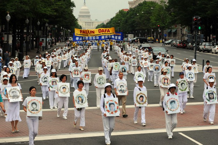 Последователи Фалуньгун несут фотографии своих единомышленников, убитых в Китае во время преследований, Вашингтон, округ Колумбия, 17 июля 2009 года. Фото: TIM SLOAN/AFP/Getty Images
