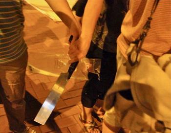 Гражданин, связанный с Hong Kong Youth Care Association (Ассоциация защиты молодёжи Гонконга), выхватил большой нож во время недавнего инцидента, когда некая группа пыталась угрожать последователям Фалуньгун. Фото: Великая Эпоха (The Epoch Times)