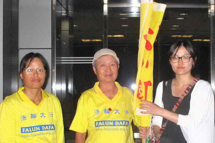 Г-жа Цай (справа), последовательница китайской духовной системы самосовершенствования Фалуньгун, с двумя друзьями около отделения полиции Tung Chung. Фото: Великая Эпоха (The Epoch Times)