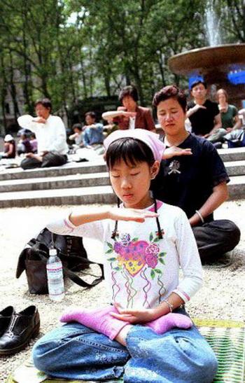 Девочка выполняет 5-е упражнение Фалуньгун в Брайант-парке 13 мая 2000 года. Фото с сайта minghui.org
