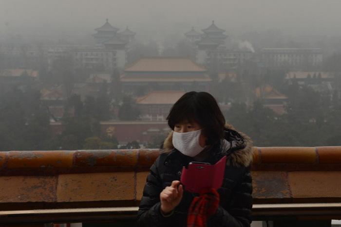 Китайская туристка в историческом парке Цзиншань надела маску, чтобы защититься от пекинского смога, 31 января 2013 года. Фото: Mark Ralston/AFP/Getty Images