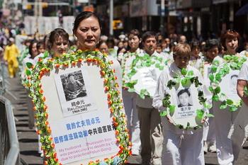 Цянь Линь идет через Чайнатаун, неся фото в память о муже, которого замучили до смерти в 2002 году. Фото: Джефф Ненарелла/Великая Эпоха (The Epoch Times)