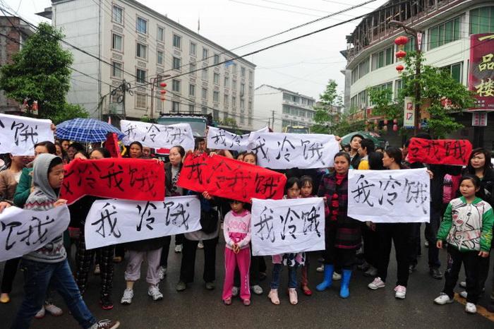 После землетрясения в юго-западной китайской провинции Сычуань, 23 апреля 2013 года жители посёлка Лингуань уезда Баосин вышли на улицу с плакатами: «Мне холодно и голодно». Они просят у властей поддержки и хотят обратить внимание на нехватку гуманитарной помощи. Фото: AFP/Getty Images