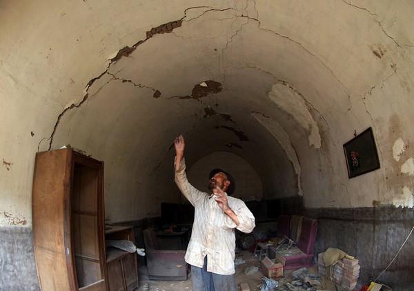 Крестьянин показывает, что его жилище начало трескаться из-за проседания почвы. Провинция Шаньси. Августа 2011 год. Фото: news.ifeng.com