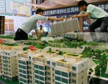 Двое рабочих устанавливают модель здания на ярмарке недвижимости, 2007 год, город Сиань, провинция Шэньси, Китай. Фото: China Photos/Getty Images