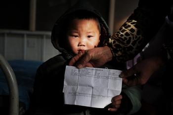 Ребёнок из провинции Аньхой показывает заключение врачей о том, что у него в крови повышено содержание свинца. Фото: STR/AFP/Getty Images