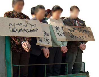 Разжигание ненависти. Последователей Фалуньгун возят по улицам в наручниках с табличками их имен на груди. Фото с minghui.com