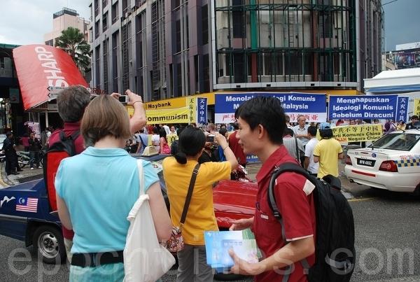 Иностранные туристы, оказавшиеся на месте событий, спешат запечатлеть момент. Фото: Zhang Jianhao/The Epoch Times
