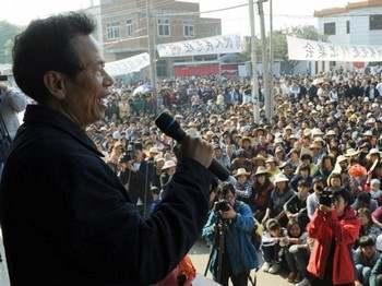 Сельские жители слушают выступление своего лидера Линь Цзулуаня (слева) на митинге, после того, как он заключил соглашение с Чжу Минго, заместителем секретаря комитета КПК провинции Гуандун, 21 декабря 2011 года. Фото: Mark Ralston /AFP /Getty Images