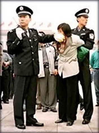 Китайские полицейские арестовывают последовательницу Фалуньгун. Фото с epochtimes.com