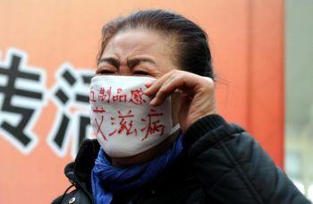 Женщина, которая заразилась при переливании крови, присоединяется к демонстрации с требованием обнародовать проблему «отрицательного ВИЧ» во Всемирный день борьбы со СПИДом на южной железнодорожной станции Пекина в 2009 году. Фото: AFP /Getty Images