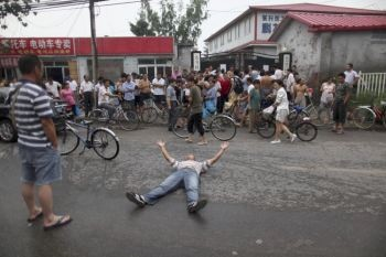 Один из родителей лежит на земле, в знак протеста против закрытия школы для детей рабочих-мигрантов в районе Хайдянь в Пекине. (фотоархив Великой Эпохи)