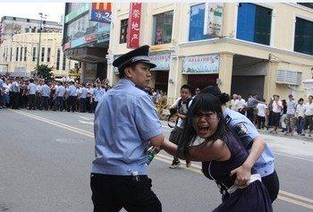 Полицейские арестовывают участницу акции в защиту кантонского диалекта в Гуанчжоу в 2010 г. Фото: The Epoch Times